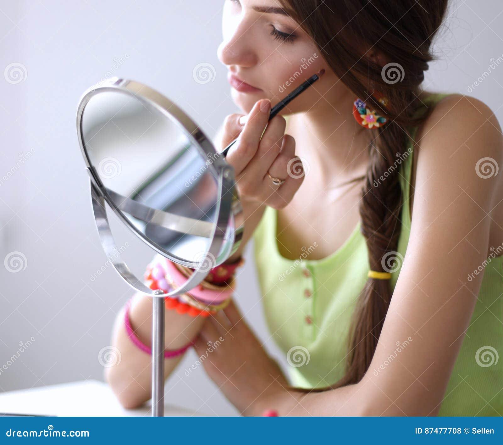 Молодая красивая женщина делая состав около зеркала