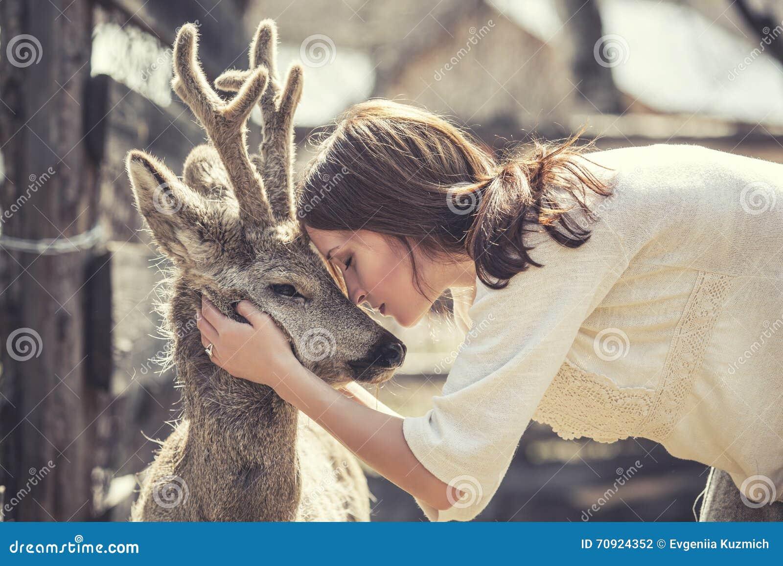 Молодая красивая женщина обнимая животных оленей КОСУЛЬ в солнечности