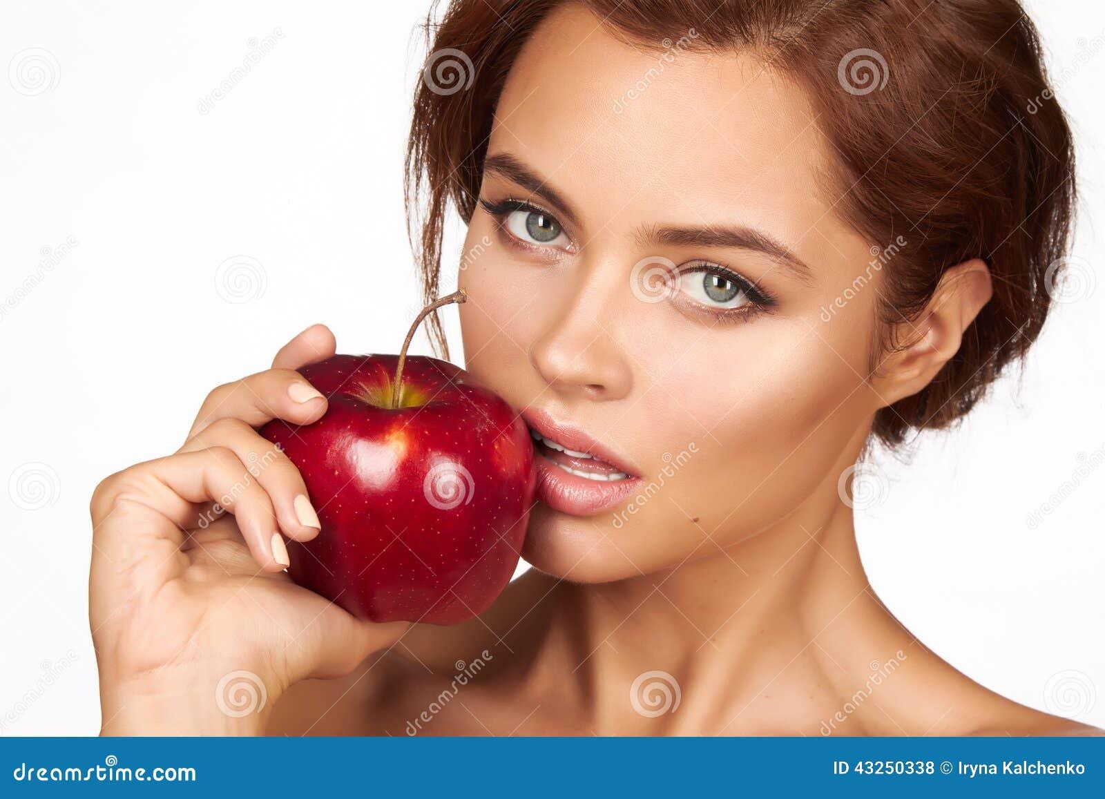 Молодая красивая сексуальная девушка при темное вьющиеся волосы, чуть-чуть плечи и шея, держа большое красное яблоко для того что