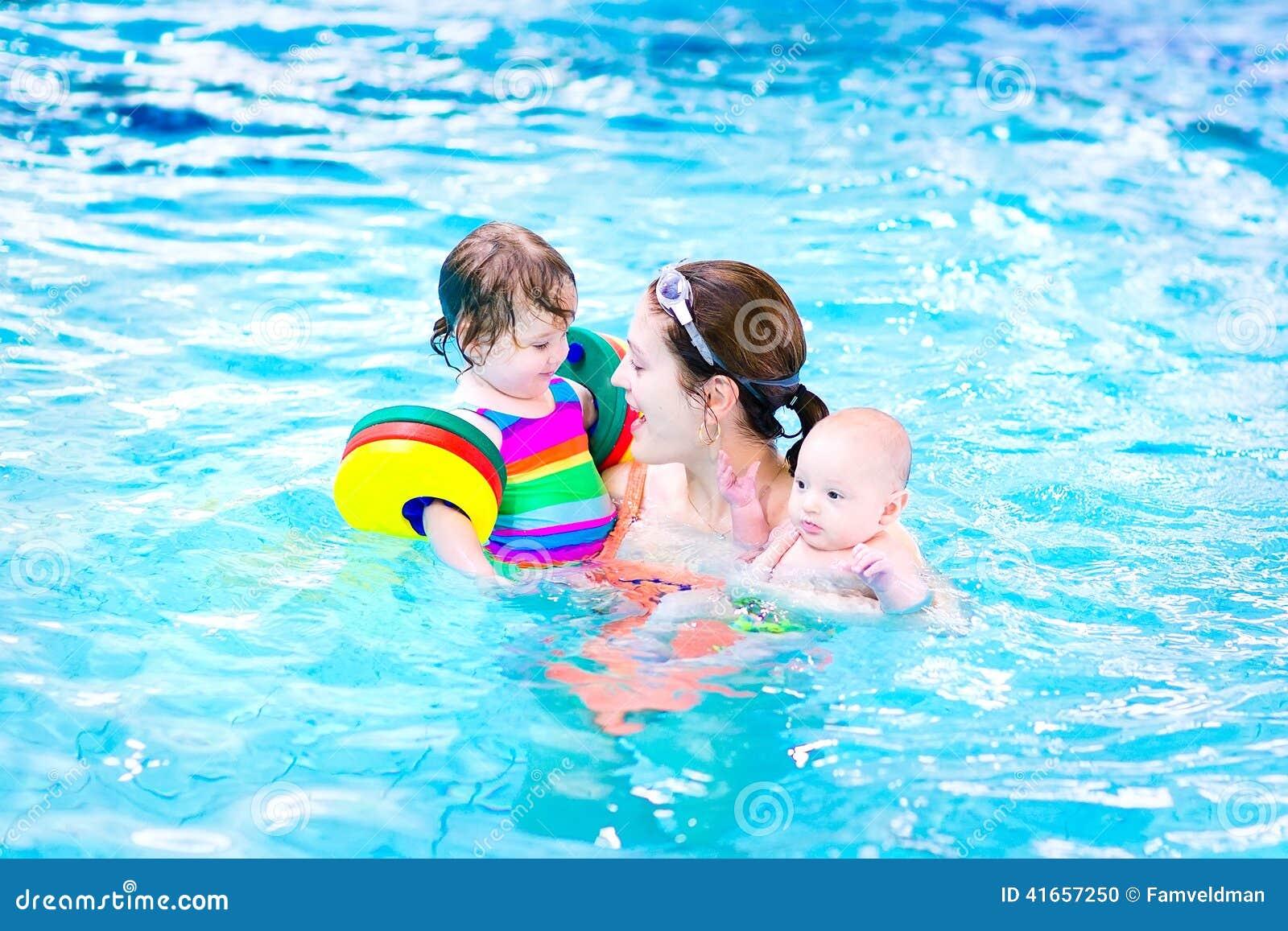 Молодая мать в бассейне с 2 детьми