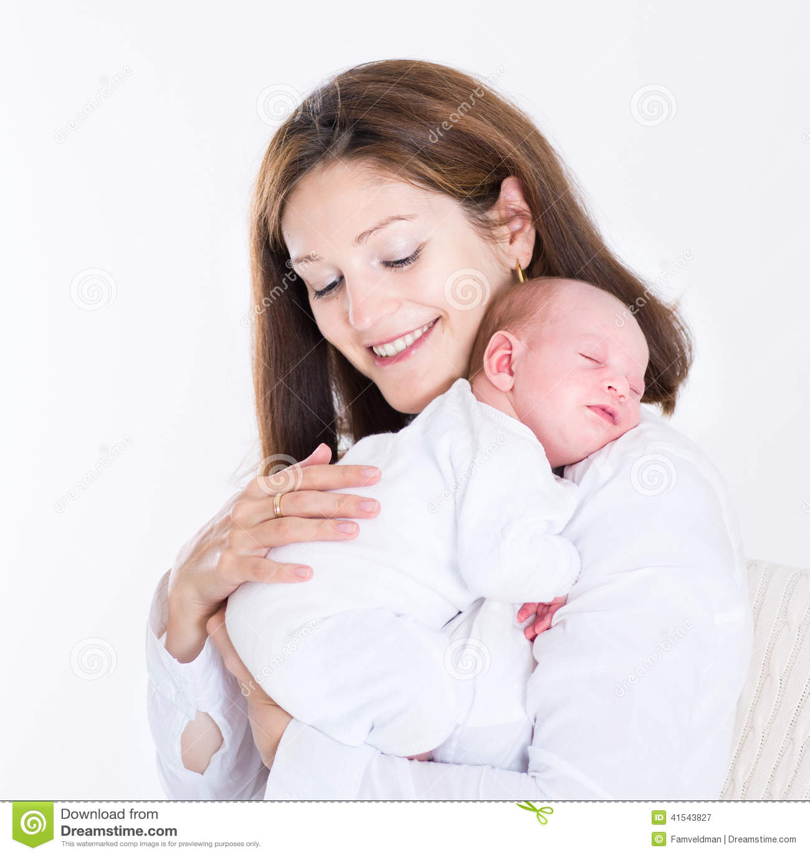 Молодая мать держа ее newborn спать младенца