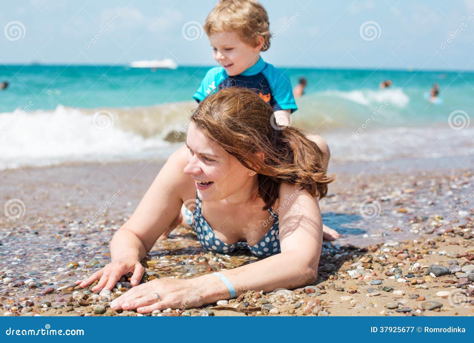 Молодая мать и маленький сын имея потеху на пляже