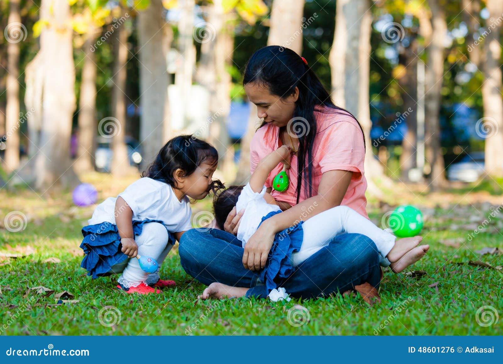 Молодая мать подавая ее младенец в парке