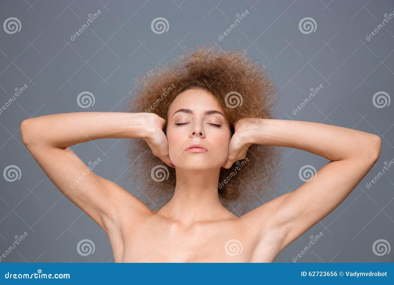 Молодая расслабленная женщина с глазами закрыла уши заволакивания руками