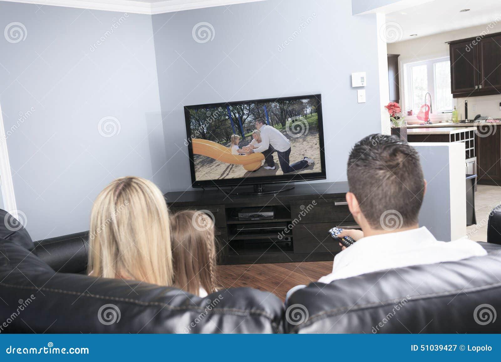 Молодая семья смотря ТВ совместно дома
