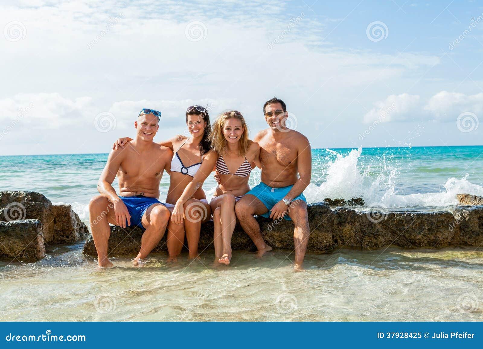 Молодая счастливая потеха havin друзей на пляже