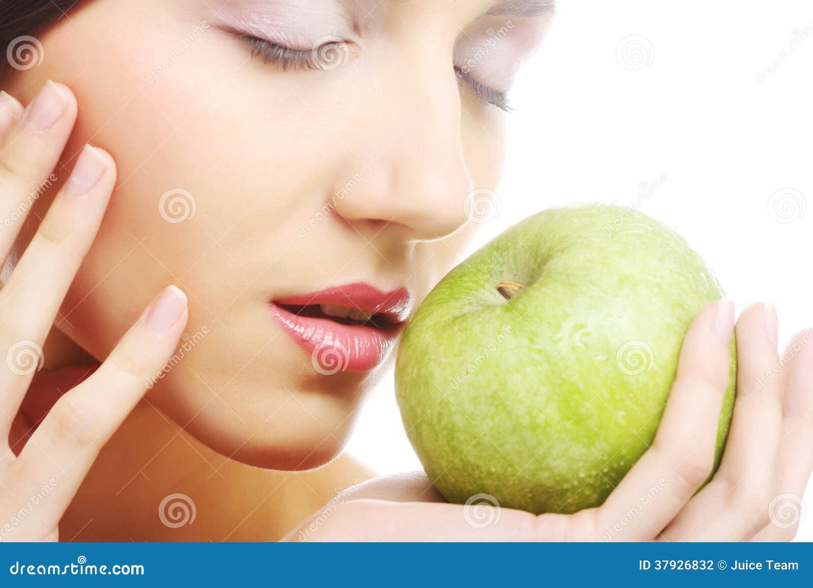 Молодая счастливая усмехаясь женщина с яблоком