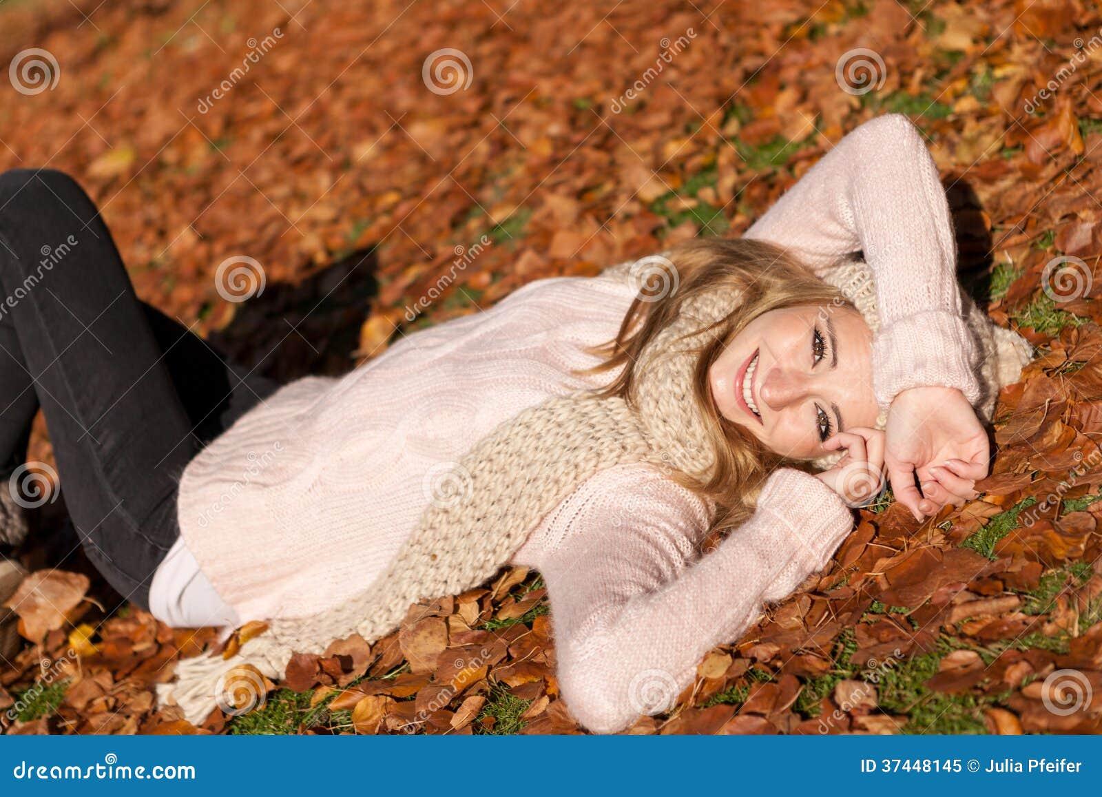 Молодая усмехаясь женщина с шляпой и шарфом внешними в осени