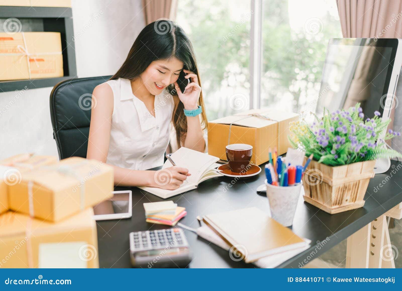 Молодое азиатское предприниматель мелкого бизнеса работая дома офис, используя мобильный телефон и принимая примечание на заказах