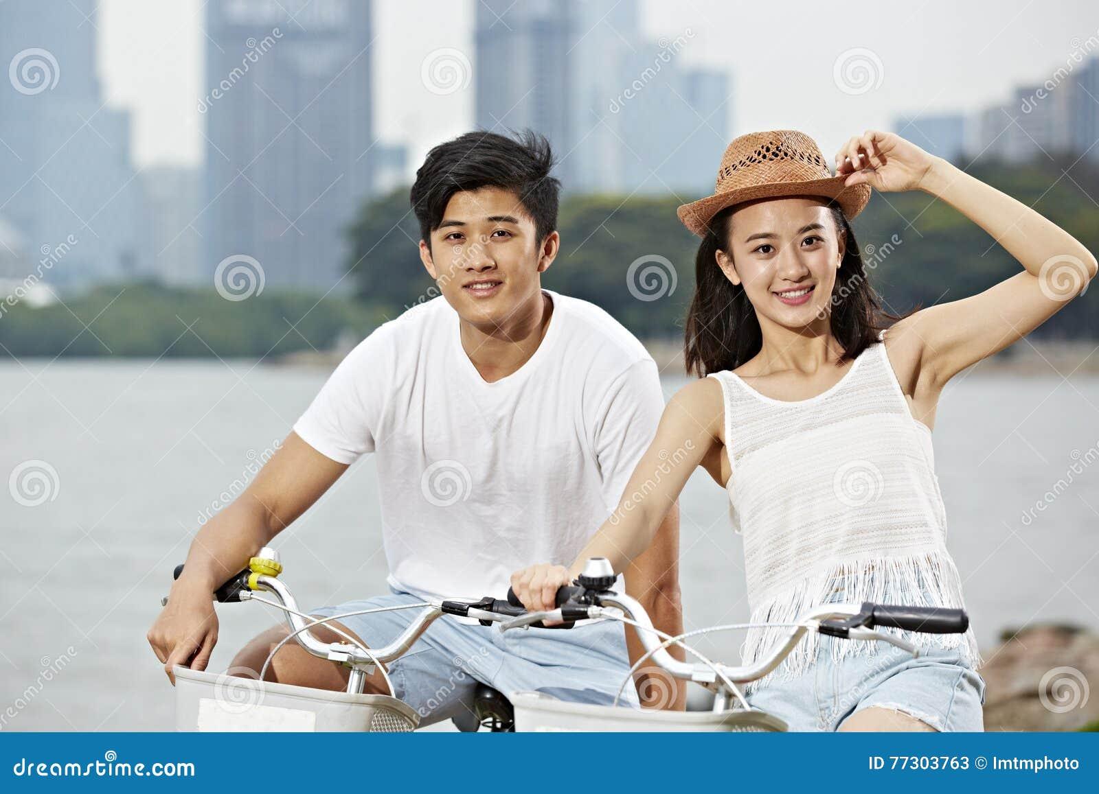 Молодой азиатский велосипед катания пар в парке города