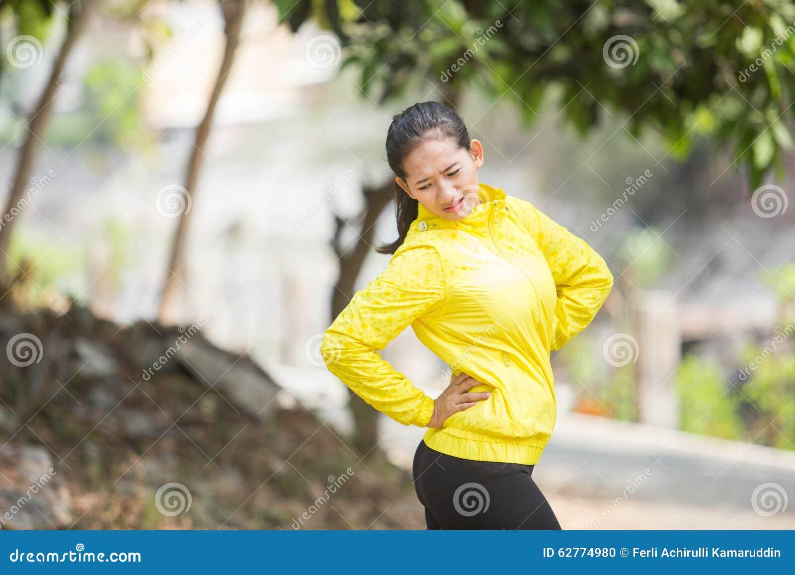 Молодой азиатский работать женщины внешний в желтой неоновой куртке с болью