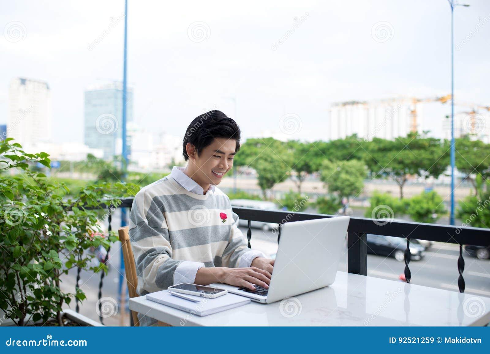 Молодой азиатский студент используя компьтер-книжку на магазине кафа города