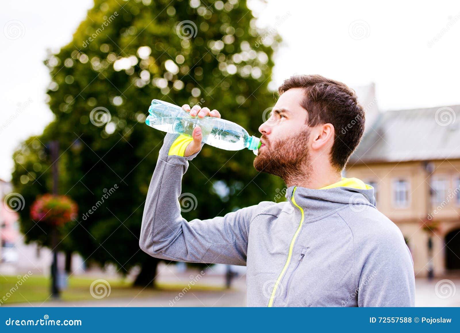 Молодой бегун битника в городке при бутылка с водой ...
