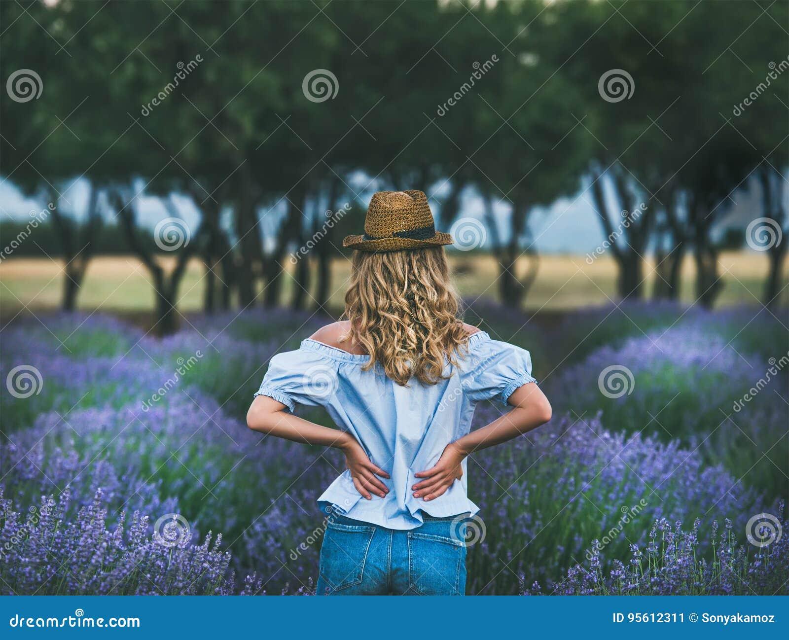 Молодой белокурый путешественник женщины стоя в поле лаванды в Турции