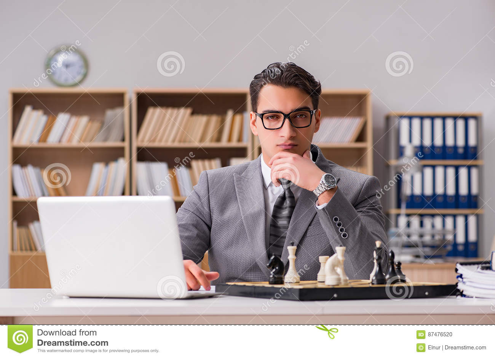 Молодой бизнесмен играя шахмат в офисе