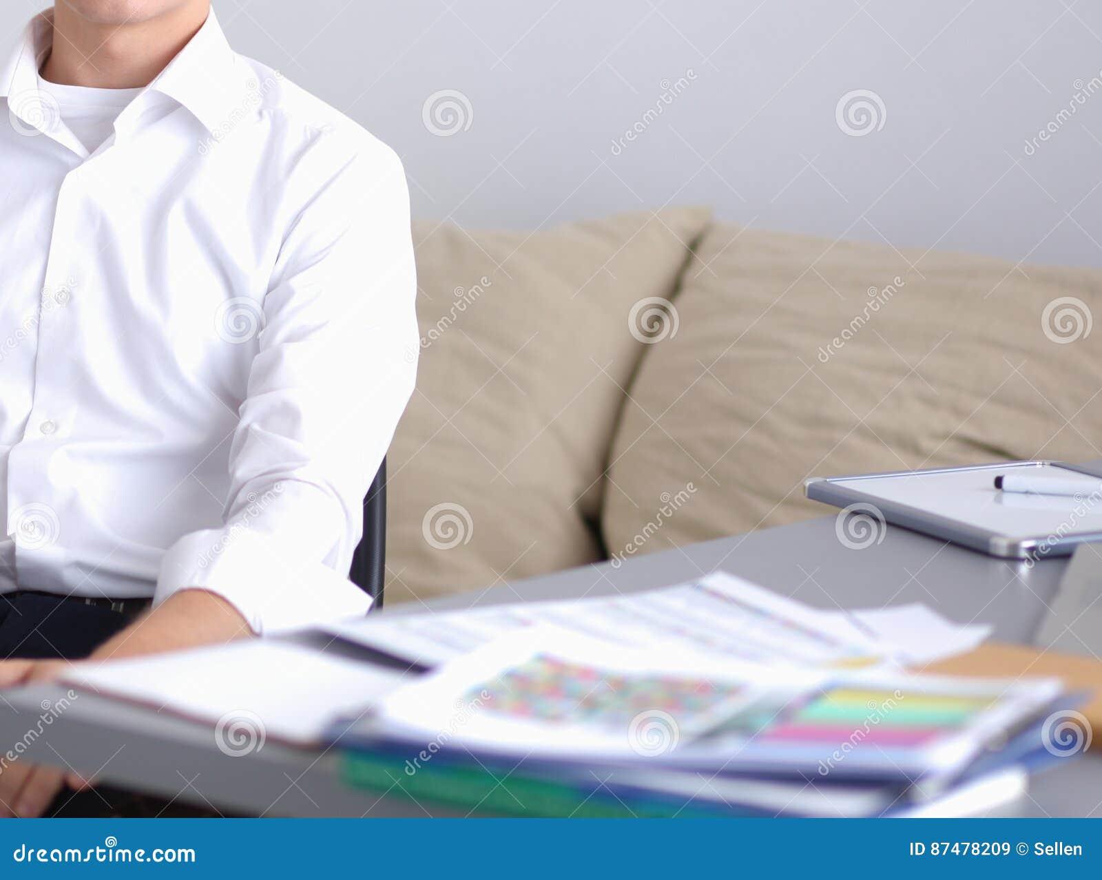 Молодой бизнесмен работая в офисе, стоя близко столе