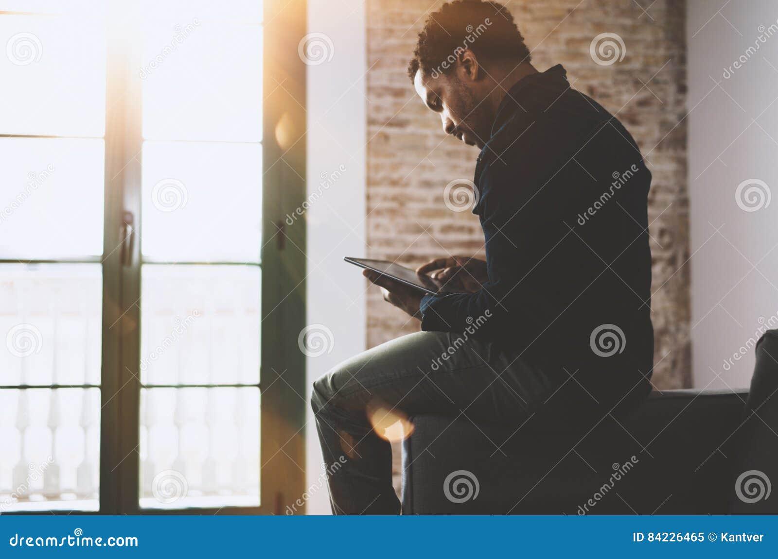 Молодой бородатый африканский человек используя компьтер-книжку пока сидящ на софе на его современном домашнем офисе Концепция лю