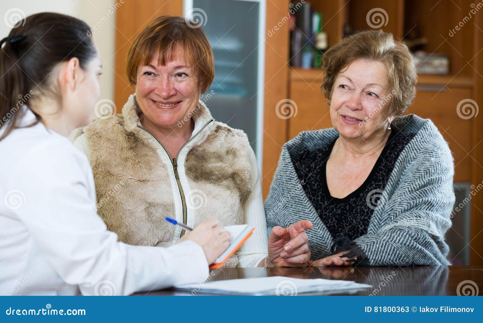 Молодой врач получая зрелых пациентов в клинике