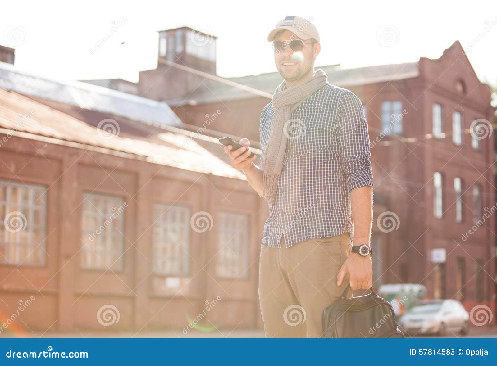 Молодой городской профессионал бизнесмена на идти smartphone
