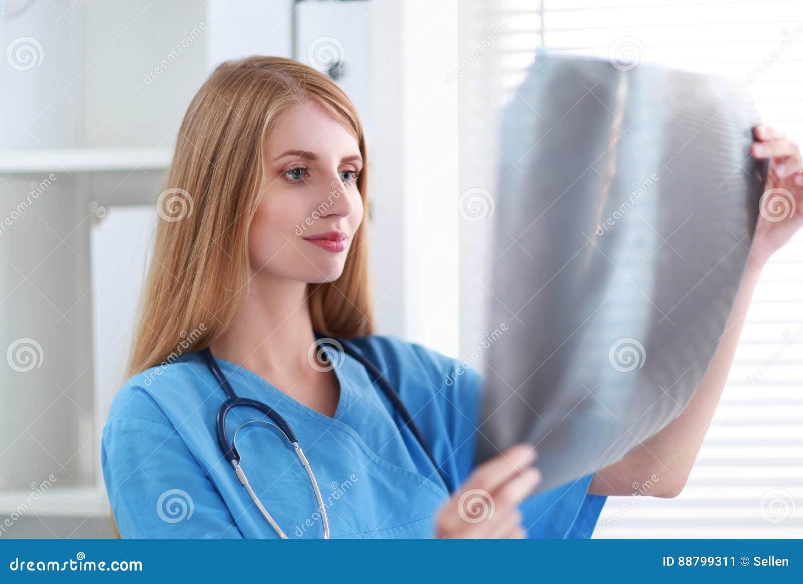 Молодой женский доктор смотря изображение рентгеновского снимка