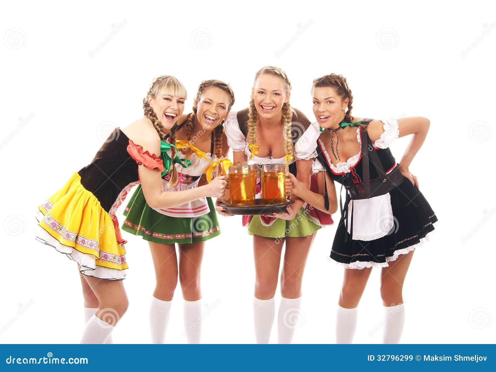 4 молодой женщины в баварских одеждах держа пиво