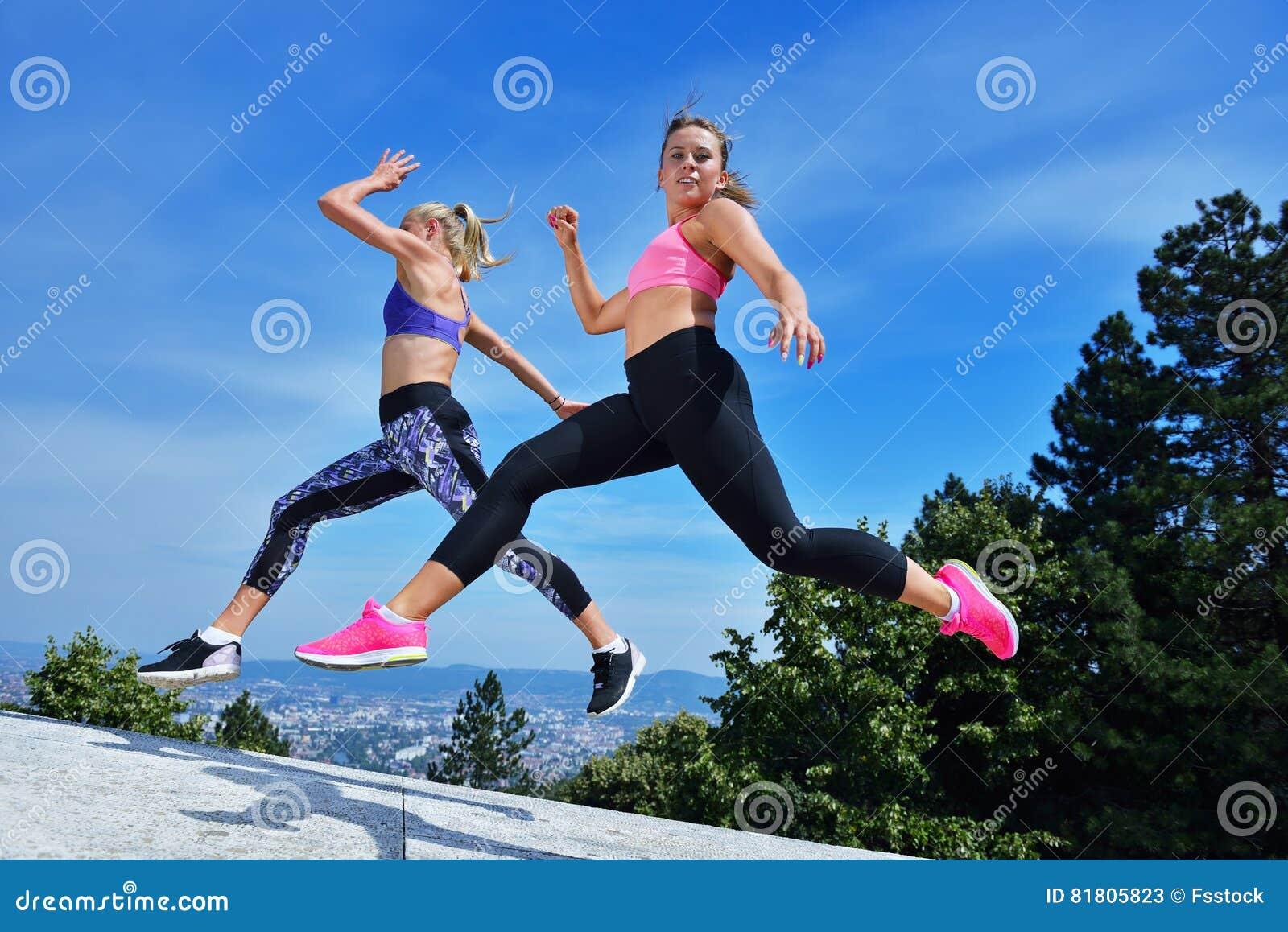 2 молодой женщины счастья скача над голубым небом