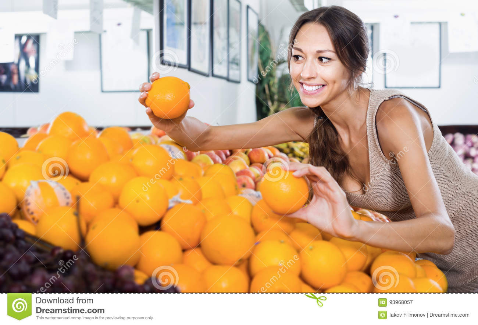 Молодой жизнерадостный клиент женщины выбирая зрелые апельсины
