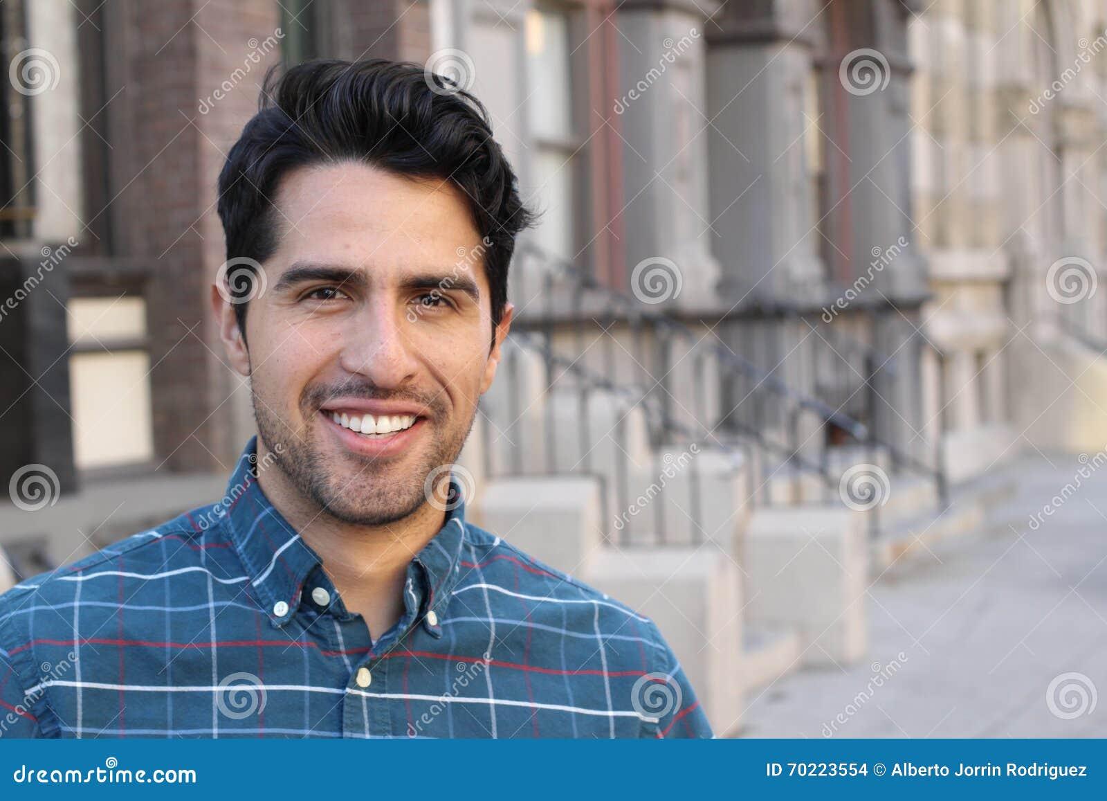 Молодой и привлекательный мужчина латиноамериканца усмехаясь в городе