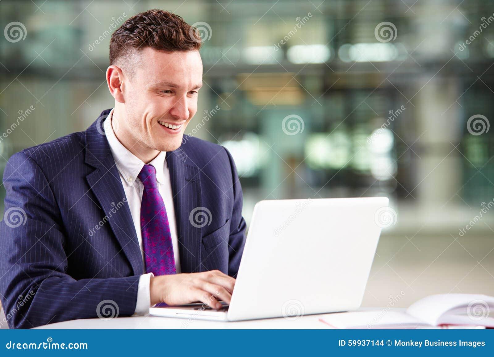 Молодой кавказский бизнесмен используя портативный компьютер на работе