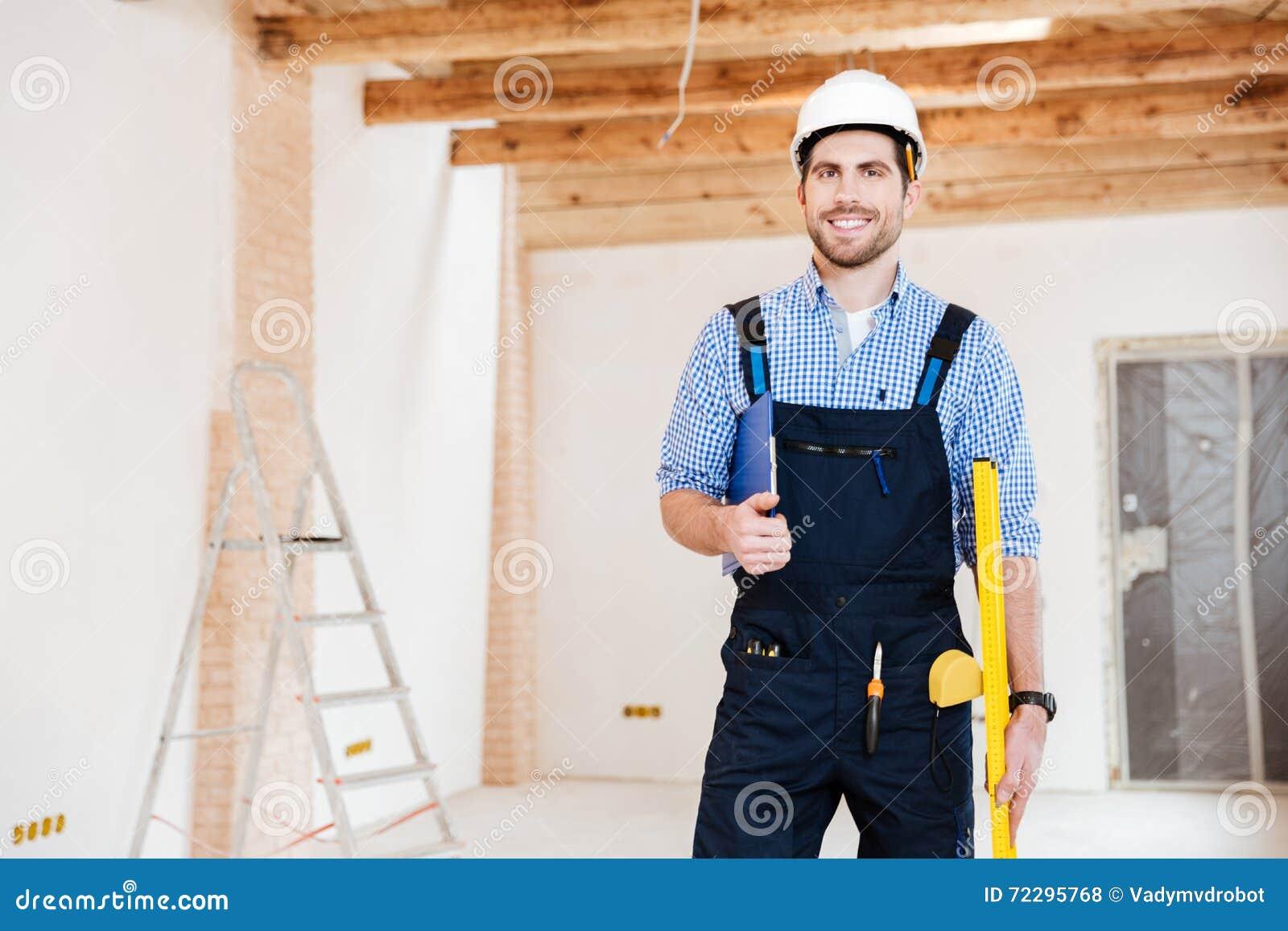 Download Молодой красивый построитель стоя и усмехаясь на месте службы Стоковое Фото - изображение насчитывающей оборудование, счастье: 72295768