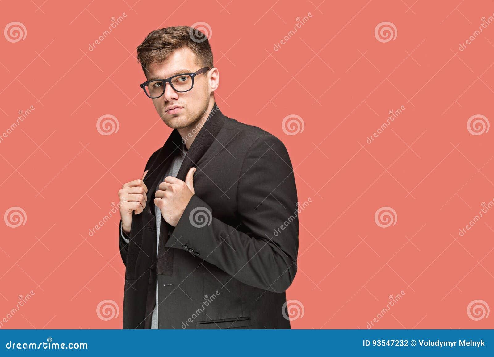 Молодой красивый человек в черном костюме и стекла изолированные на красной предпосылке