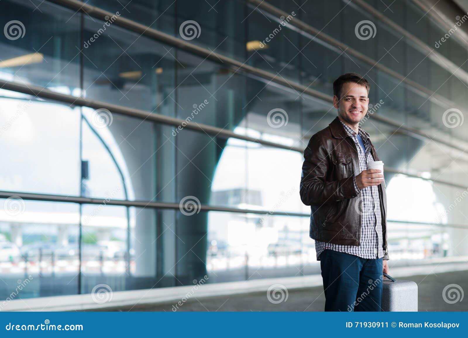 Молодой красивый человек с кофейной чашкой и чемоданом в авиапорте