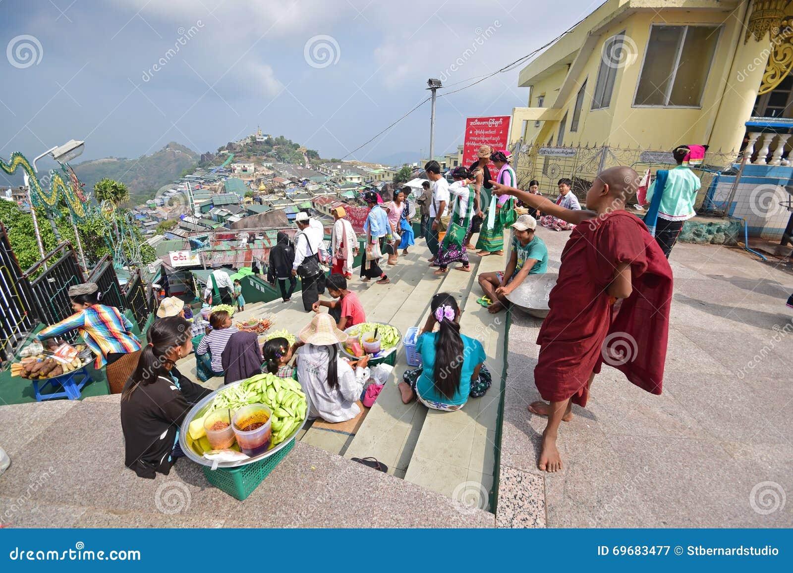 Молодой маленький буддийский монах указывая где-то afar пока паломники проходя мимо & поставщики продавая закуски вдоль лестниц