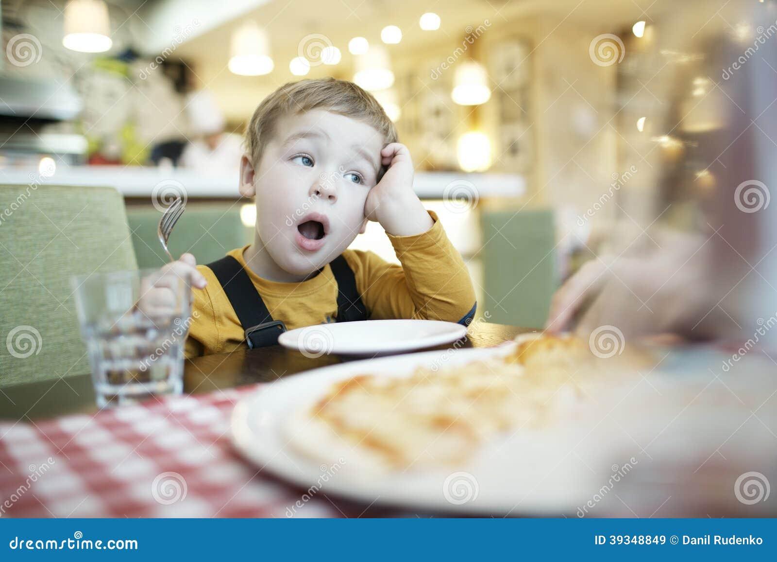 Молодой мальчик зевая по мере того как он ждет быть поданным