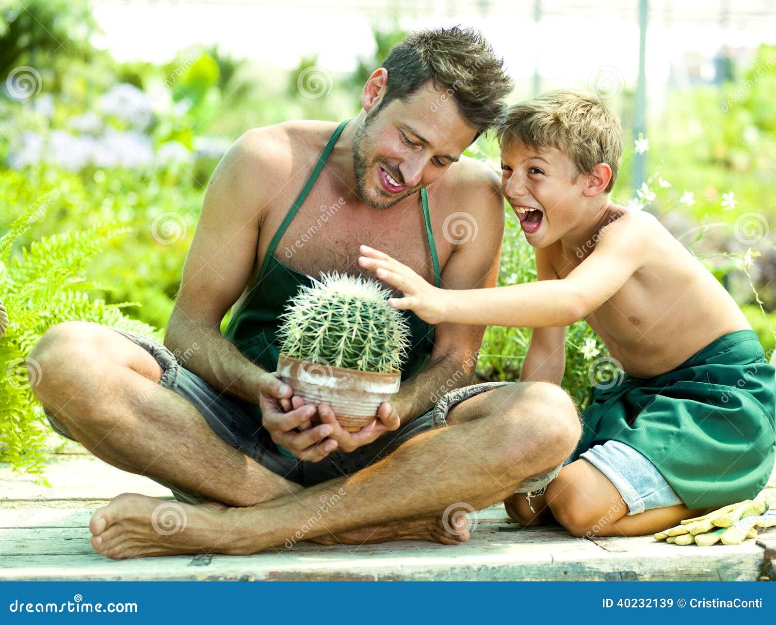 Молодой мальчик играя с его отцом в парнике