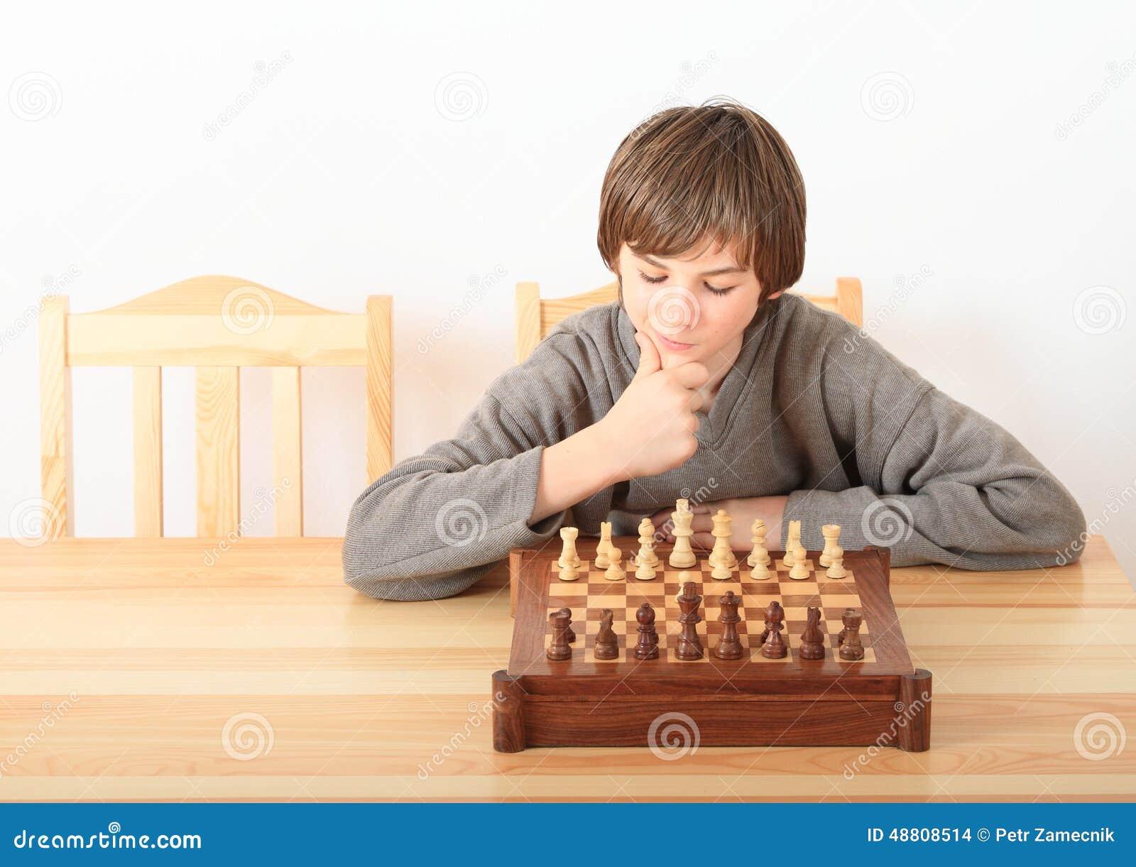 Молодой мальчик играя шахмат
