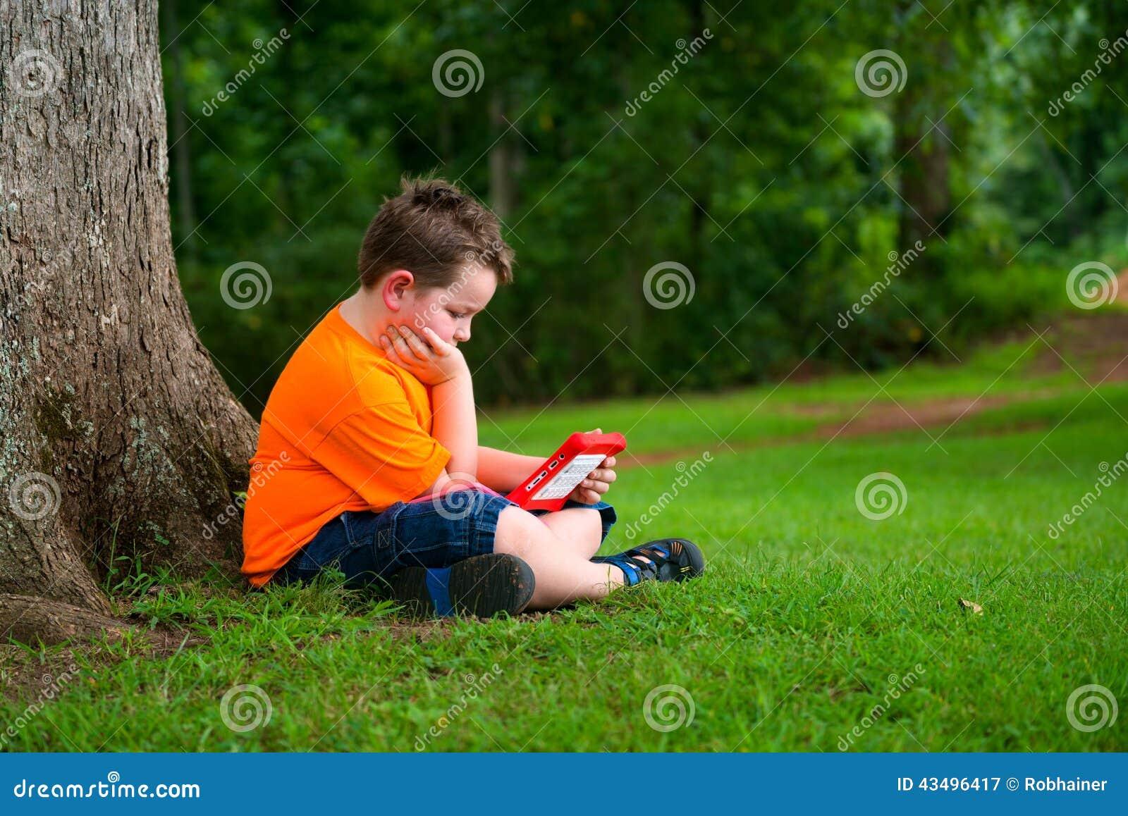 Молодой мальчик используя таблетку outdoors