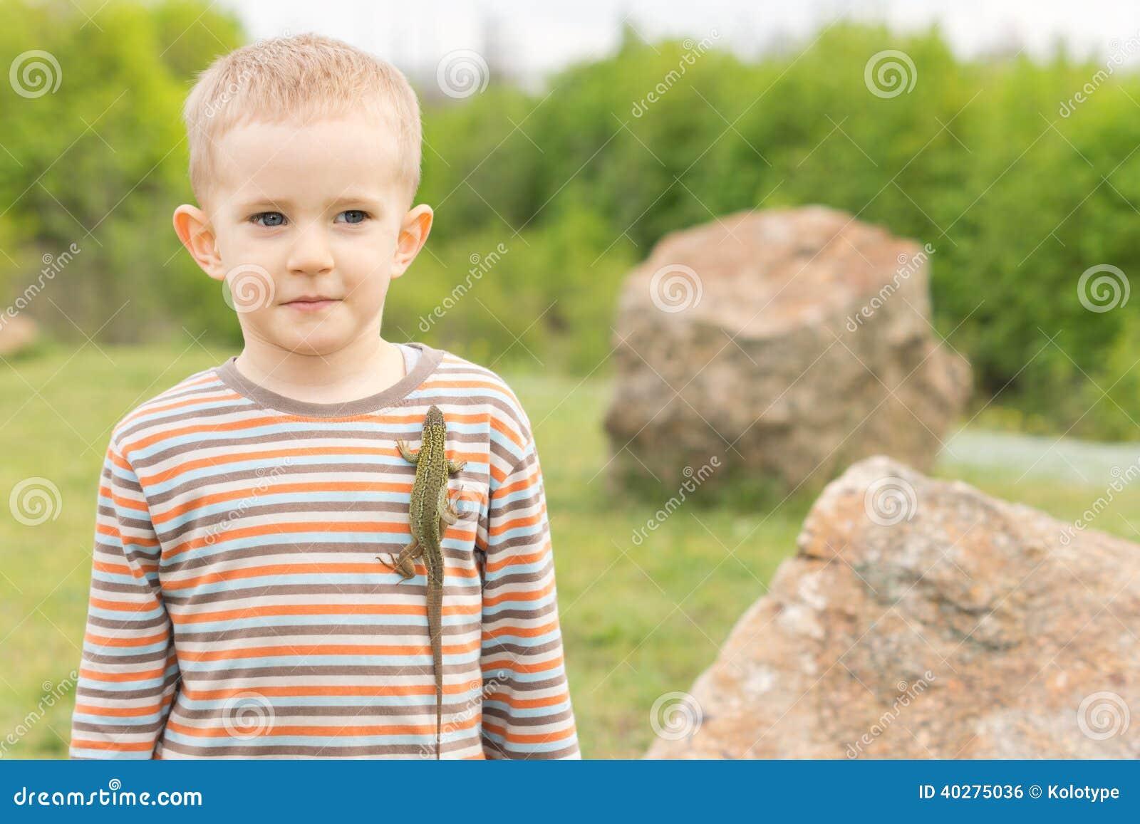 Молодой мальчик позволяющ ящерице вползти на его рубашке