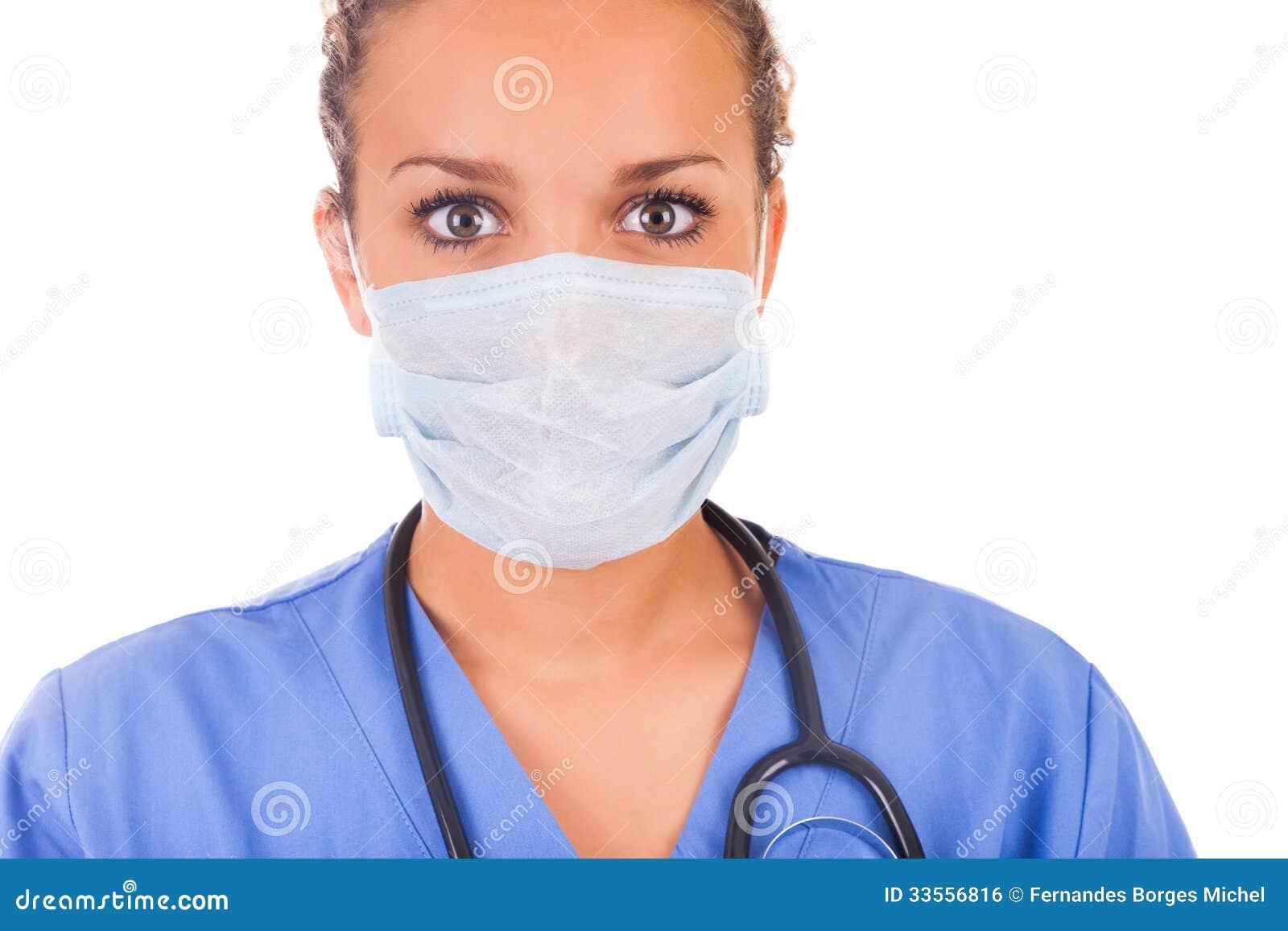 Молодой доктор при маска и стетоскоп изолированные на белом backgro