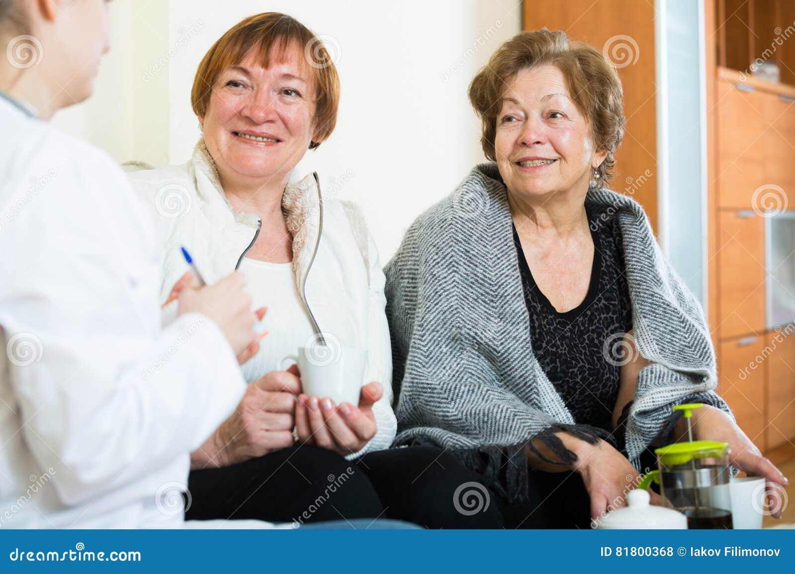 Молодой доктор советуя с старшими petients в отечественном интерьере