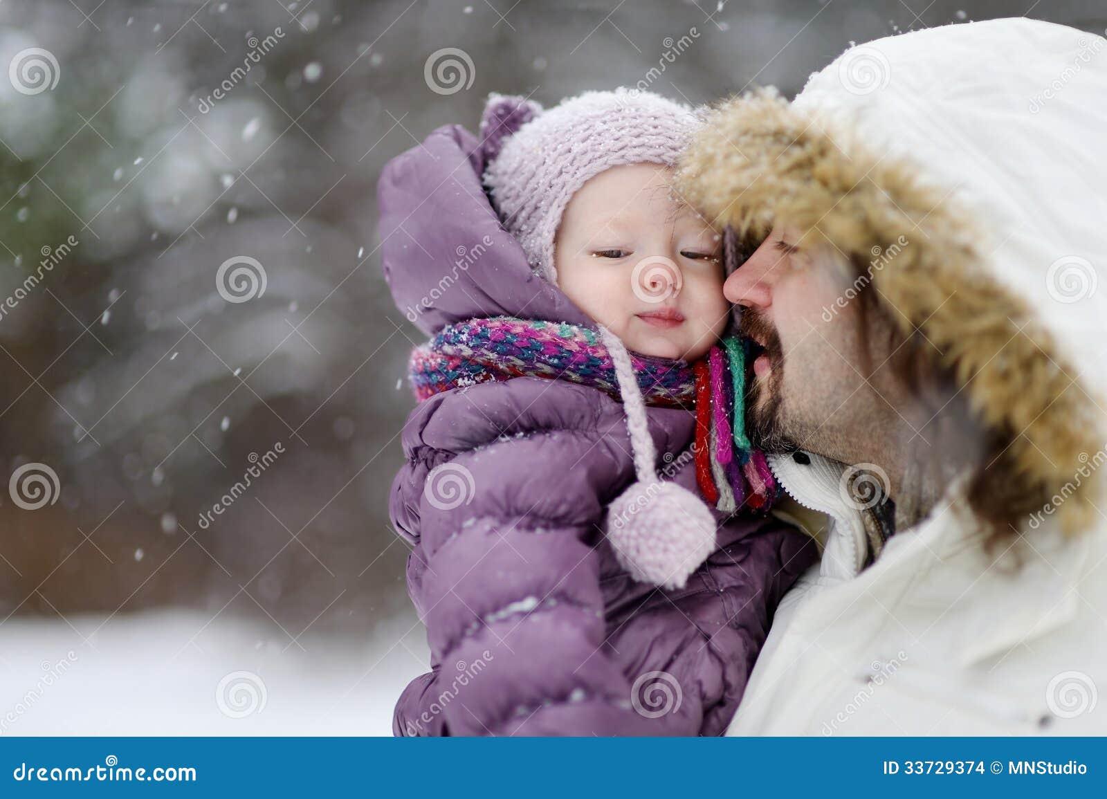 Молодой отец и его дочь на зимнем дне