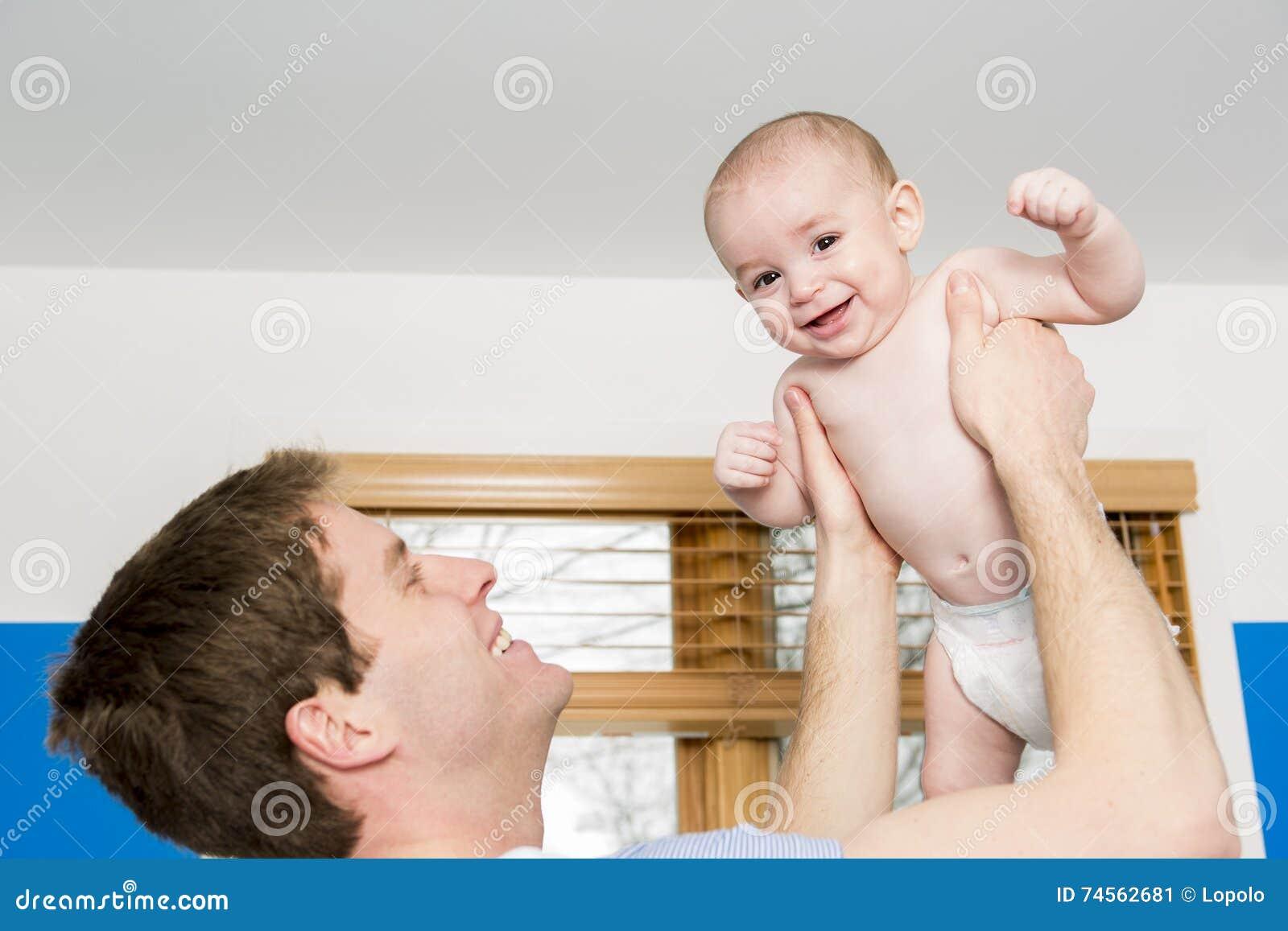 Молодой папа держа его сына в оружиях