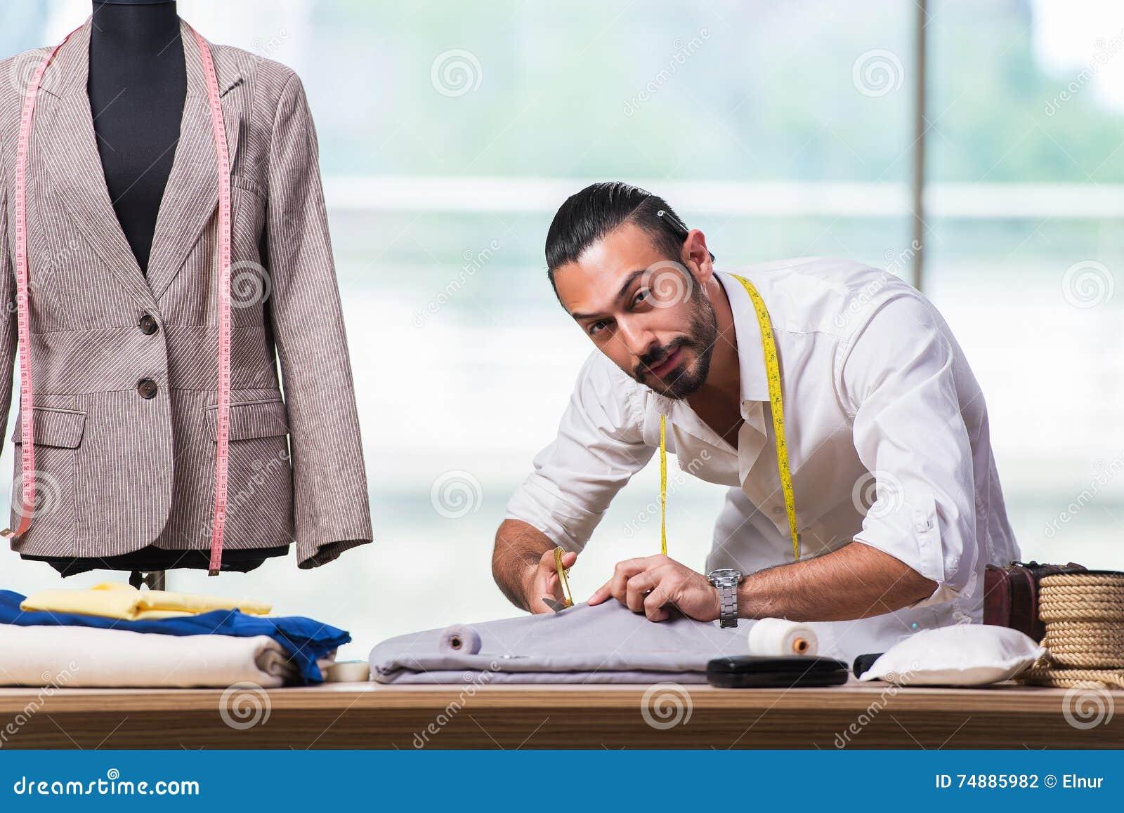 Молодой портной работая на новом дизайне одежды