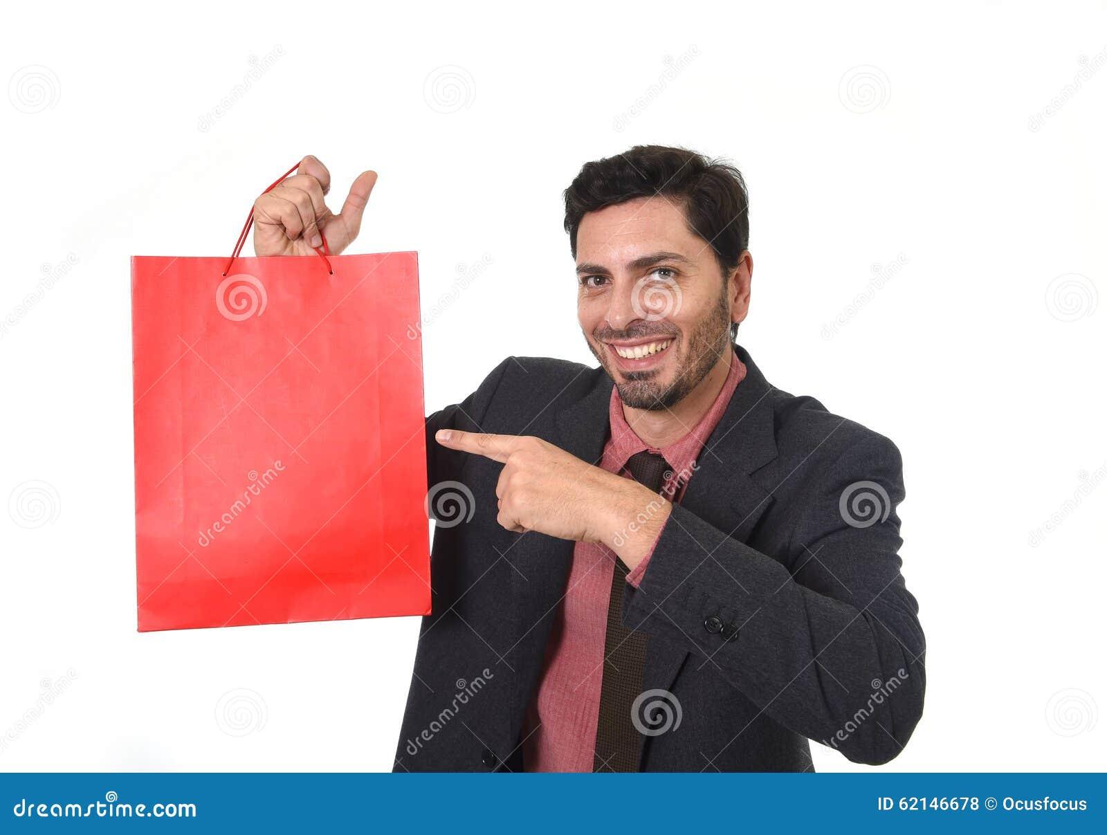 Молодой привлекательный бизнесмен держа и указывая красную хозяйственную сумку в концепции продажи выполняя как продавец