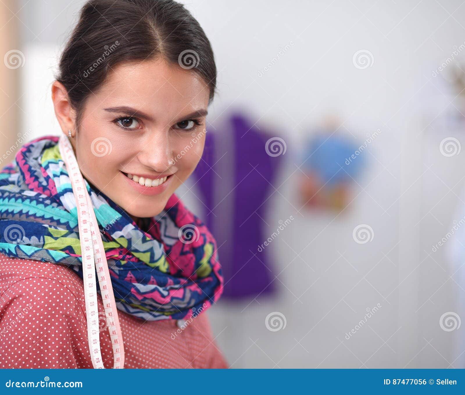 Молодой привлекательный женский модельер работая на столе офиса, рисуя пока говорящ на черни