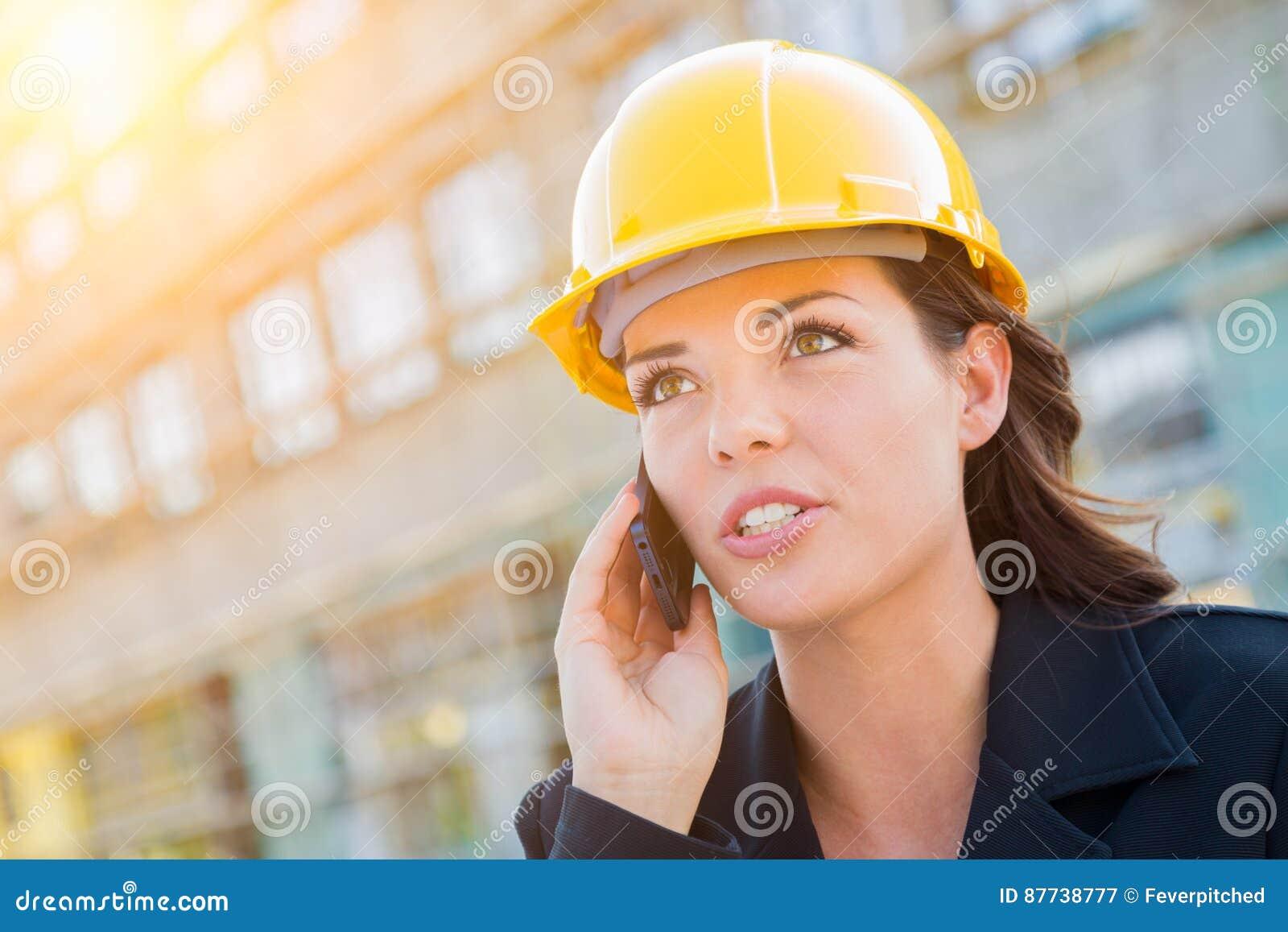 Молодой профессиональный женский подрядчик нося трудную шляпу на Contruc