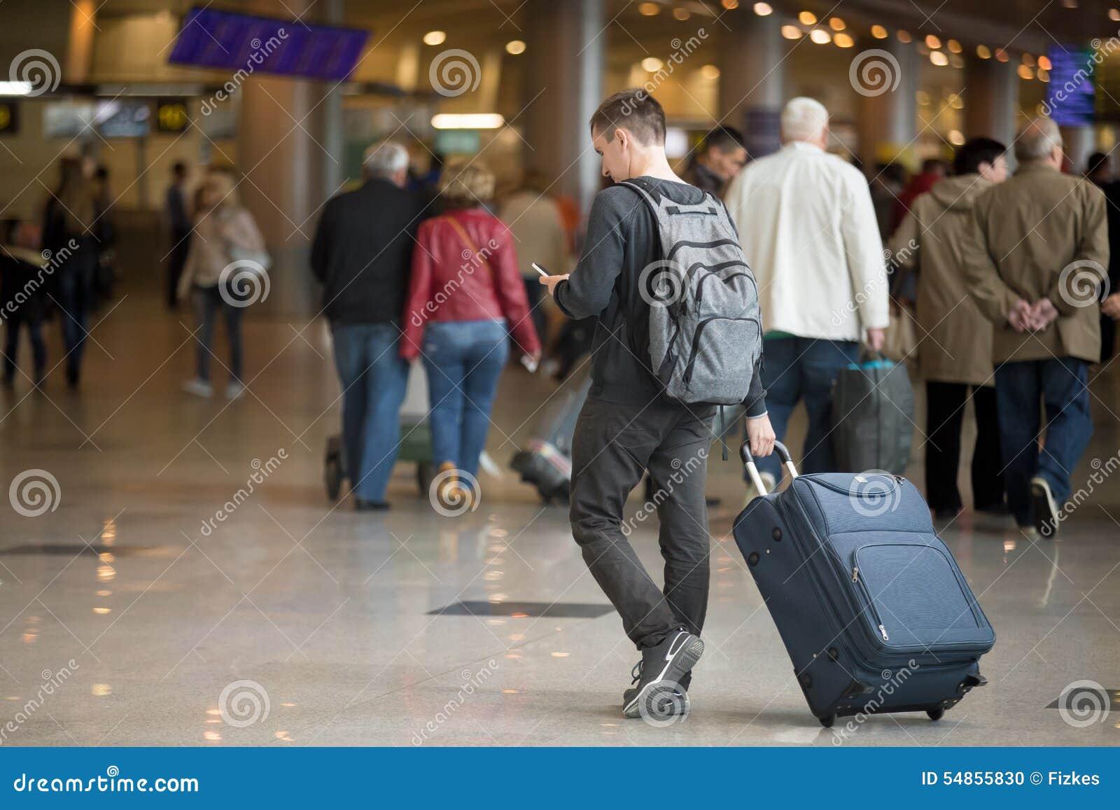 Молодой путешественник с smartphone в авиапорте