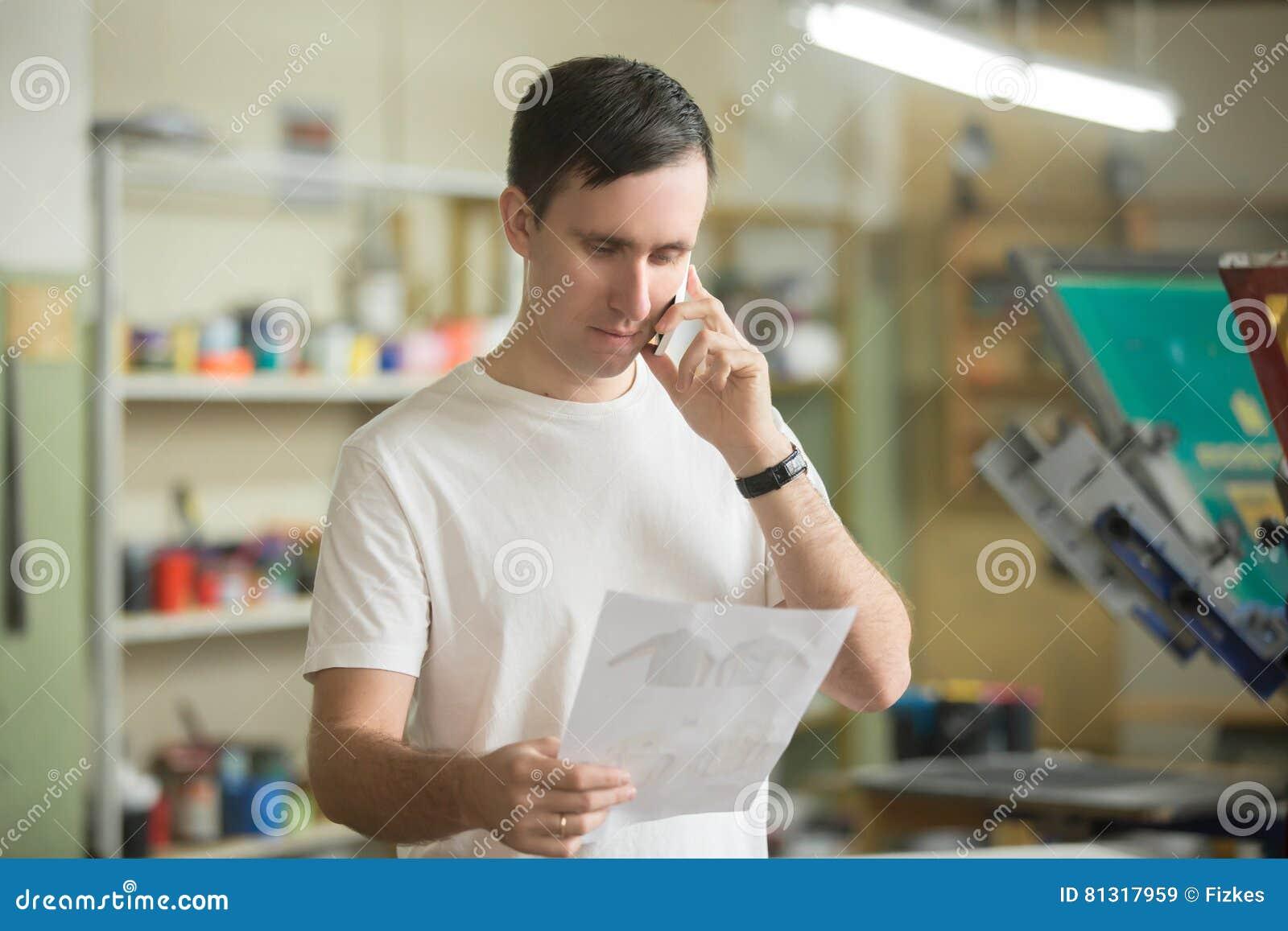 Молодой работник говоря на телефоне