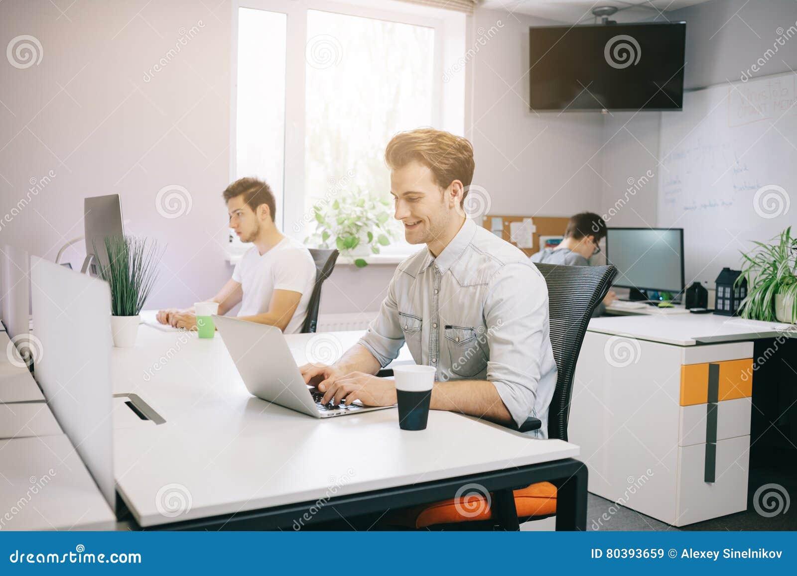 Молодой работник сидя в офисе на компьютере Фрилансер в белой рубашке Дизайнер сидит перед окном внутри