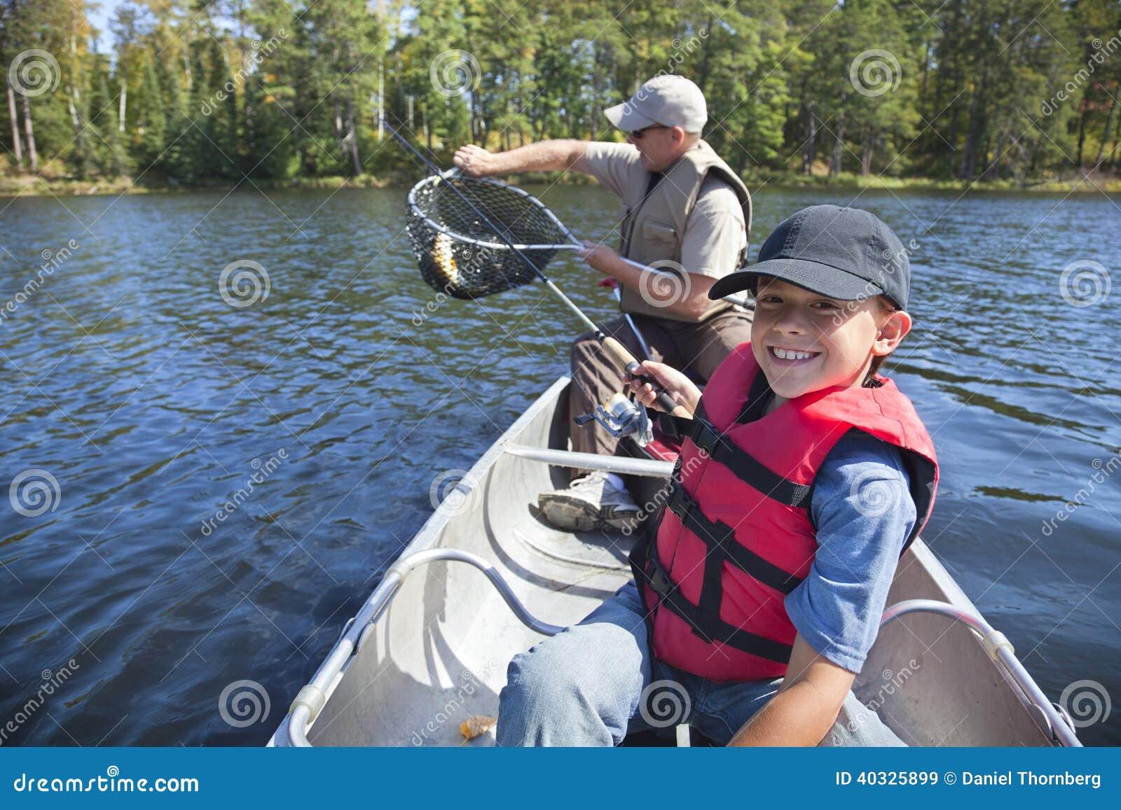 Молодой рыболов мальчика усмехается на задвижке славных walleye